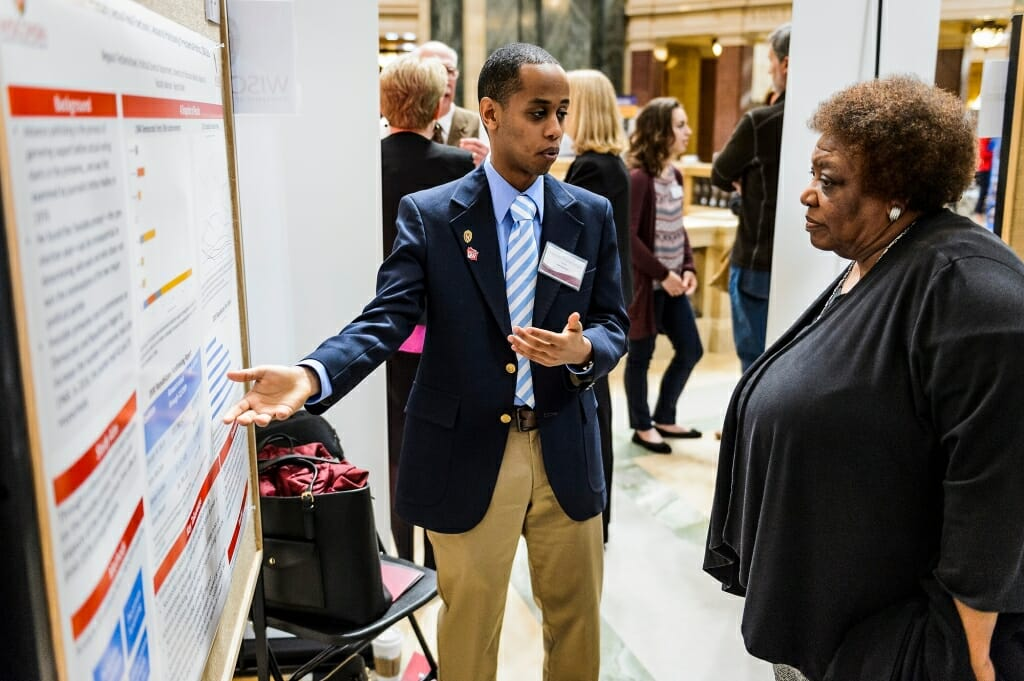 UW-Madison student Negassi Tesfamichael describes his research project on display to Gloria Hawkins, assistant vice provost and director of Chancellor's Scholars and Powers Knapp's Scholarship Programs.