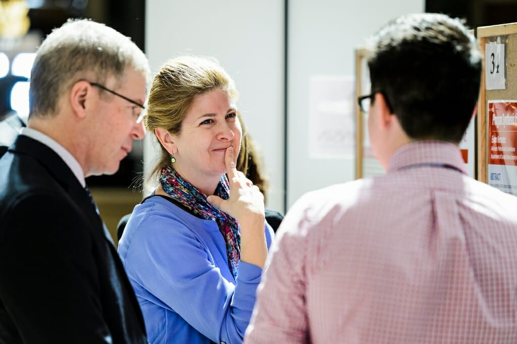 Steven Cramer, UW-Madison vice provost for teaching and learning, and Michelle Harris, faculty associate in the Biology Core Curriculum, listen to Evan Hernandez talk about his research project.