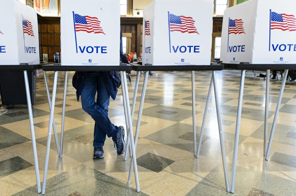 A person's leg's seen under a row of voting booths with American flags and the word