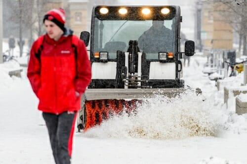 Photo: Snow brush vehicle following pedestrian