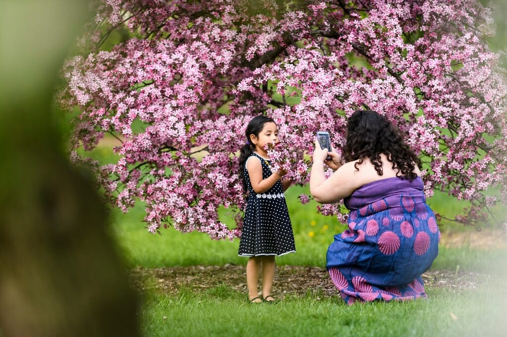 Photo: Woman taking photo of young girl in front of tree