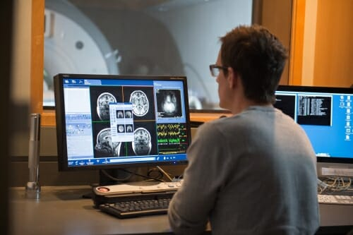 Photo: Unidentified researcher looking at brain scan images on computer screen