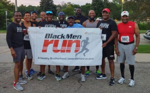 Photo of Black Men Run members posing with banner.