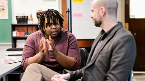 Photo: A UW program director talking with a high school student as part of a humanities outreach program