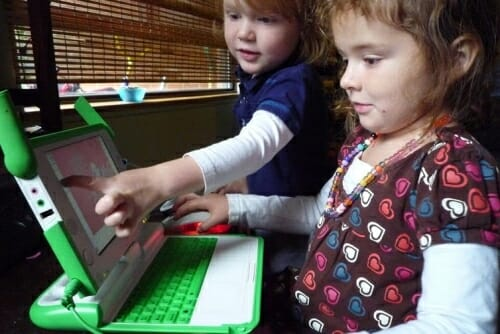 Photo: 2 young girls working at a green laptop computer