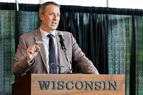 Photo of John Horn speaking at a podium.