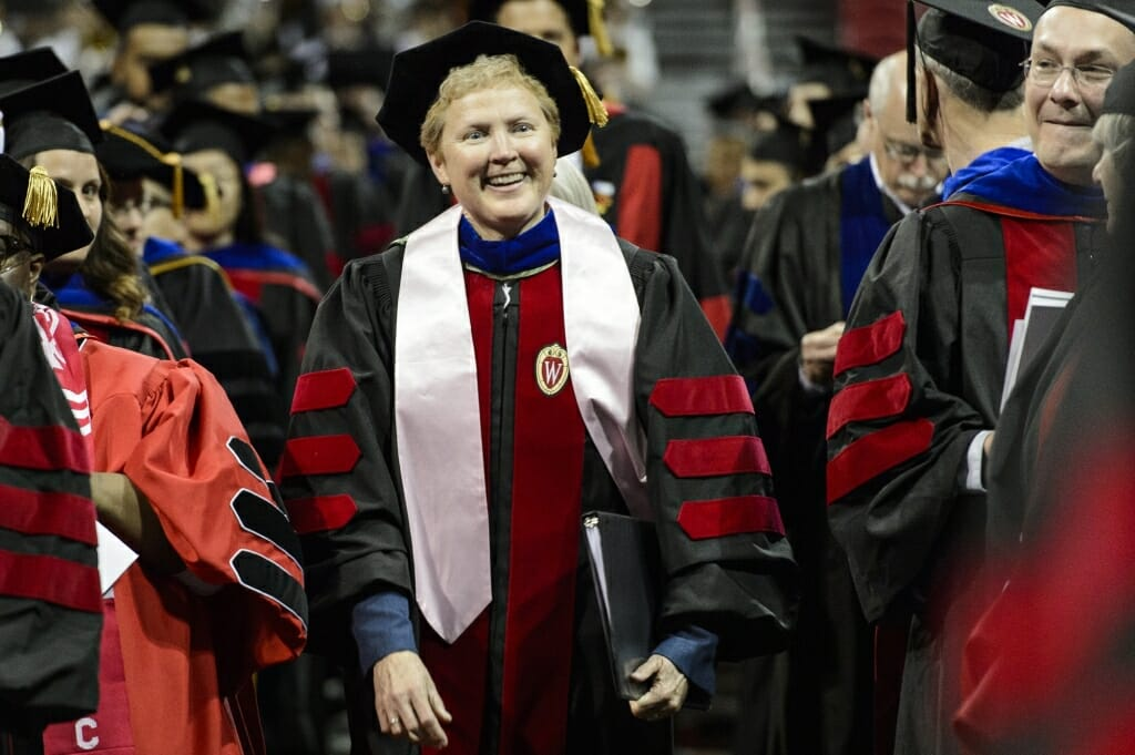 Photo of Dean of Students Lori Berquam walking towards the stage during UW-Madison's spring commencement ceremony Friday at the Kohl Center.
