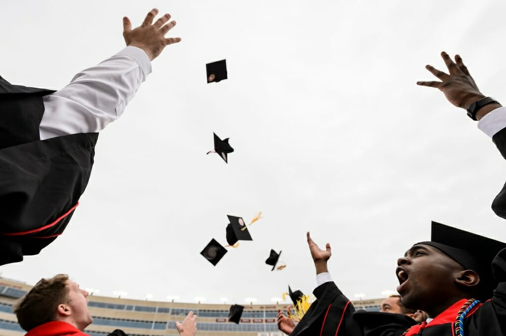 Photo of graduates tossing caps into the air.