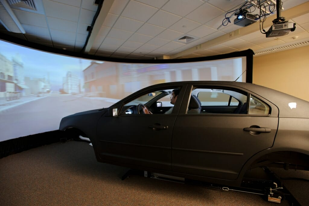 Photo: Man in car simulating driving in front of projection screen