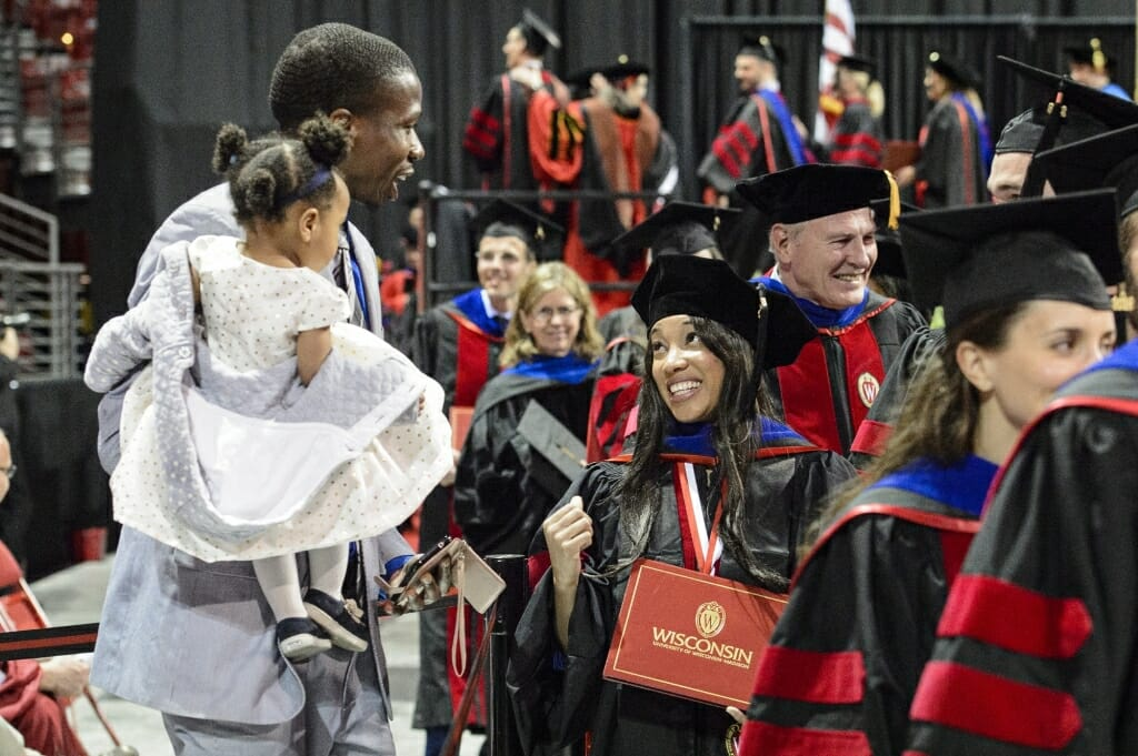Photo of a graduate sharing a smile with her family after walking the stage.