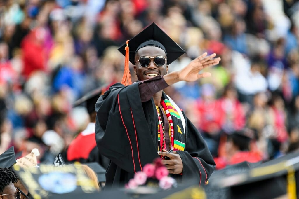 Photo of Charles Fatunbi, graduating with a bachelor's degree in industrial engineering, waving to the crowd.