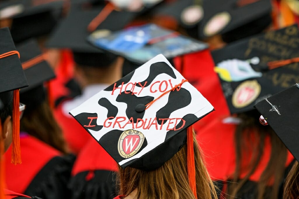 Photo of a Holstein-patterned mortarboard that reads,