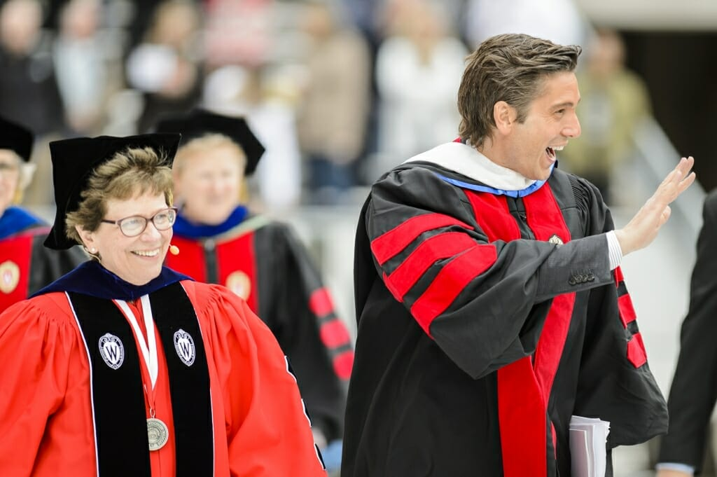 Photo of Photo of commencement speaker David Muir, an Emmy-winning journalist, and Chancellor Rebecca Blank walking among the graduates at Camp Randall Saturday.