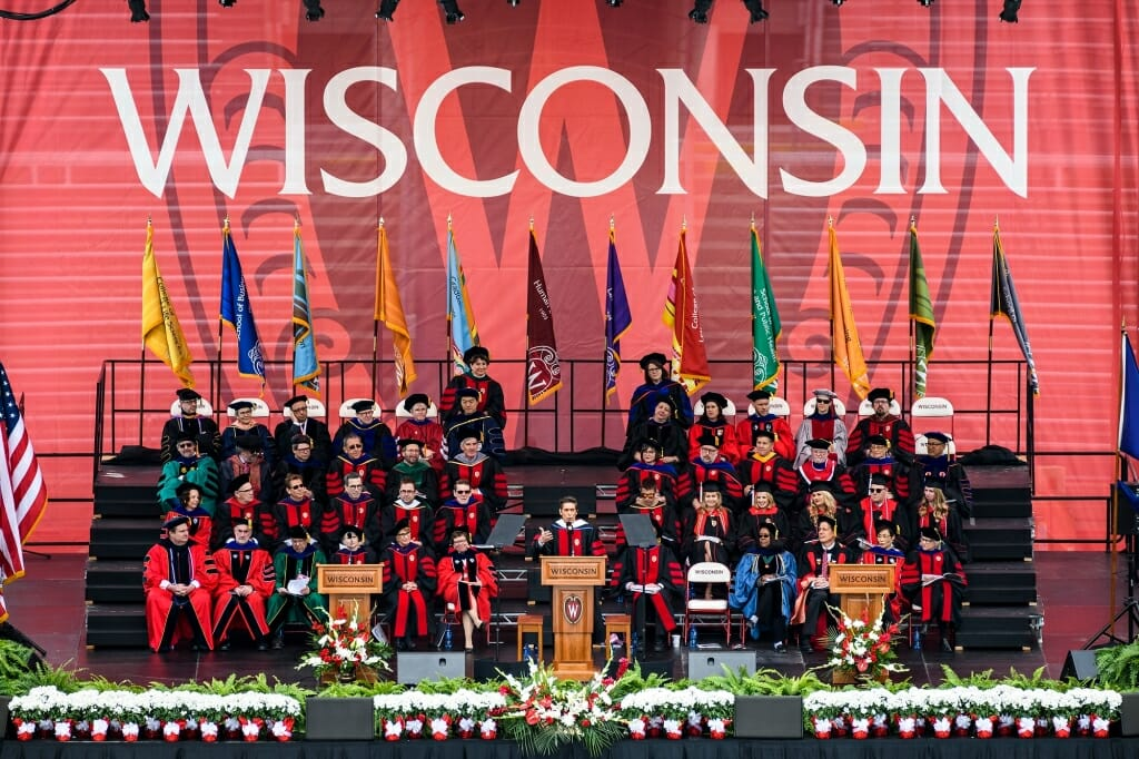 Photo of speaker David Muir flanked by the platform party of university leaders and senior class officers.