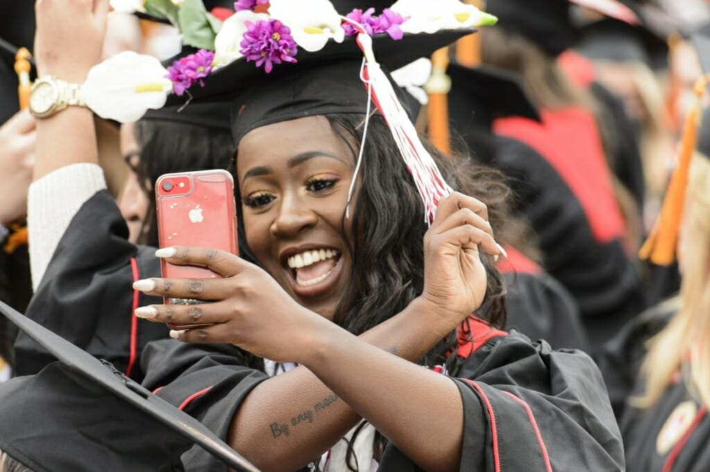 Photo of a student recording herself flipping her tassel to indicate she has graduated.
