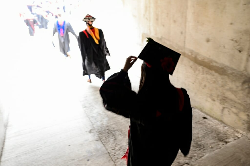 Photo of a graduate adjusting her mortarboard before walking through a tunnel to enter Camp Randall for Saturday's ceremony.