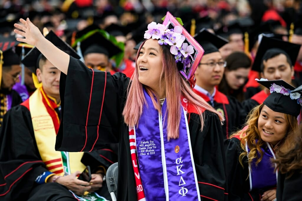 Photo of Kimberly Vue, a first-generation graduate and daughter of Hmong refugees, waving to her family.