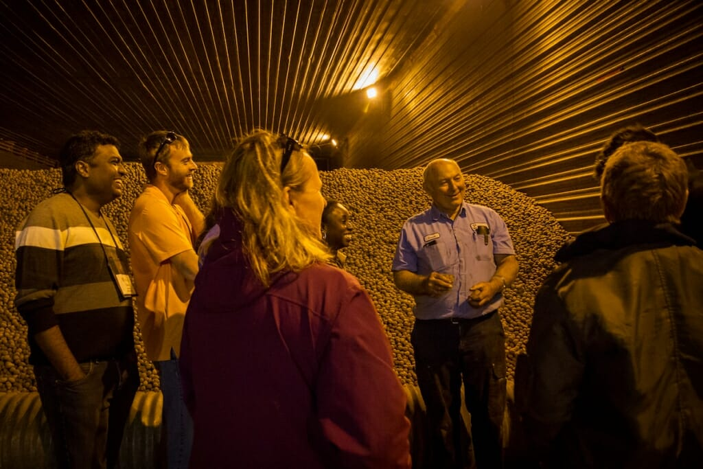 Photo: Farmer standing with group in front of potato pile