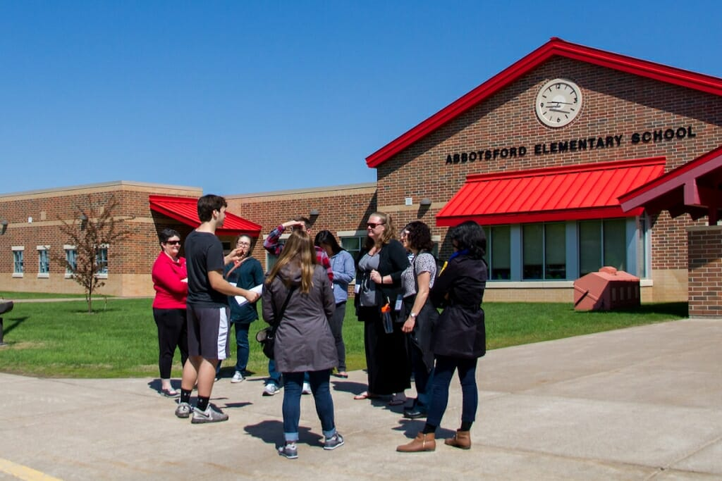 Photo: Student with visitors outside school building