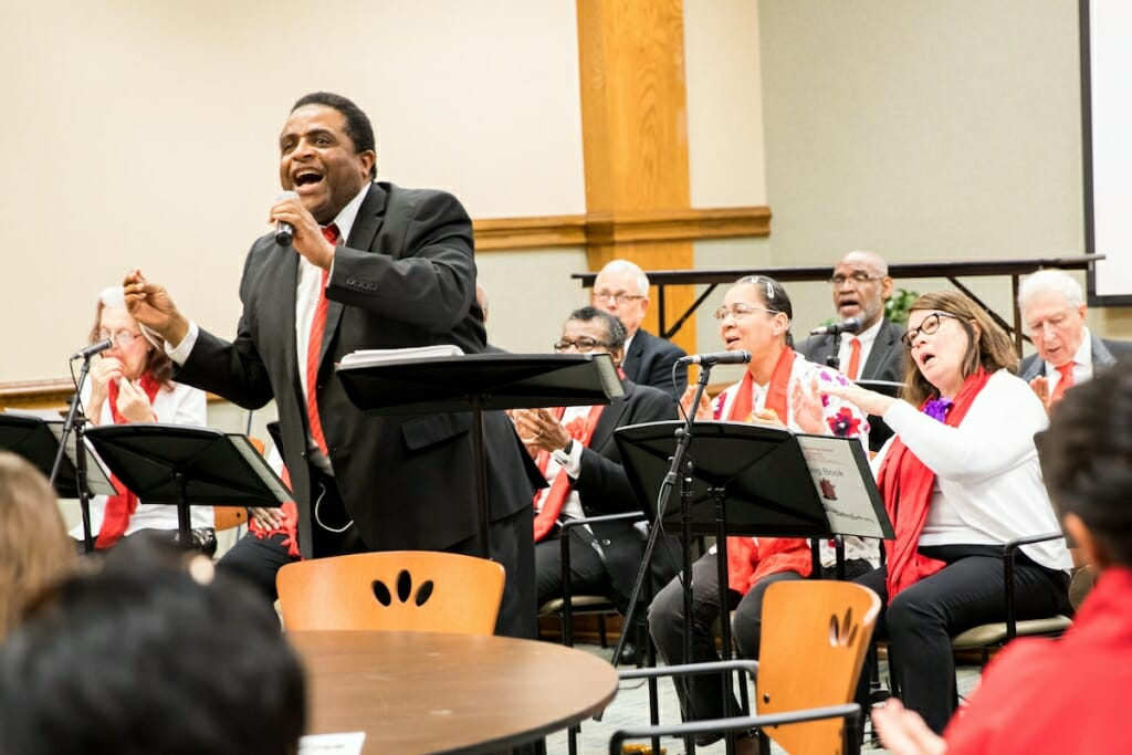 Photo: K.C. Williams singing into a microphone with people playing instruments