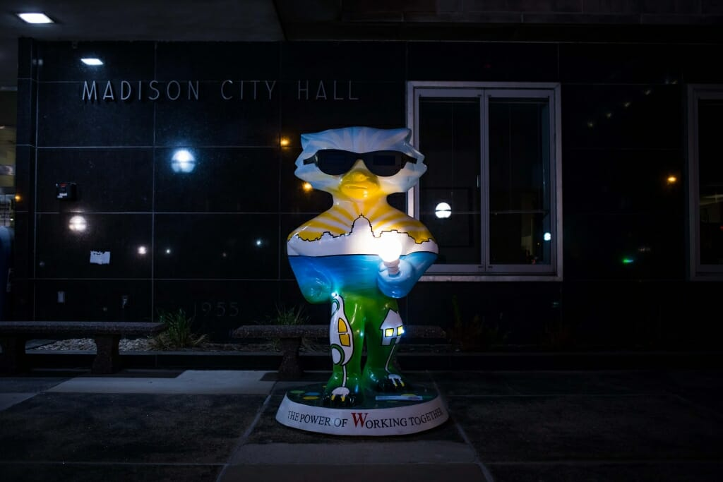 """A photo of """"Bucky Energized"""" photographed at night. The statue, also designed by Hustad, is sponsored by Madison Gas and Electric and features a functional flashlight gripped in Bucky's paw."""