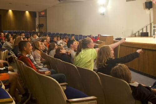 Photo: Students in auditorium pointing at stage