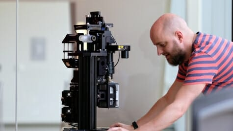 Photo: Researcher looking at microscope on lab bench