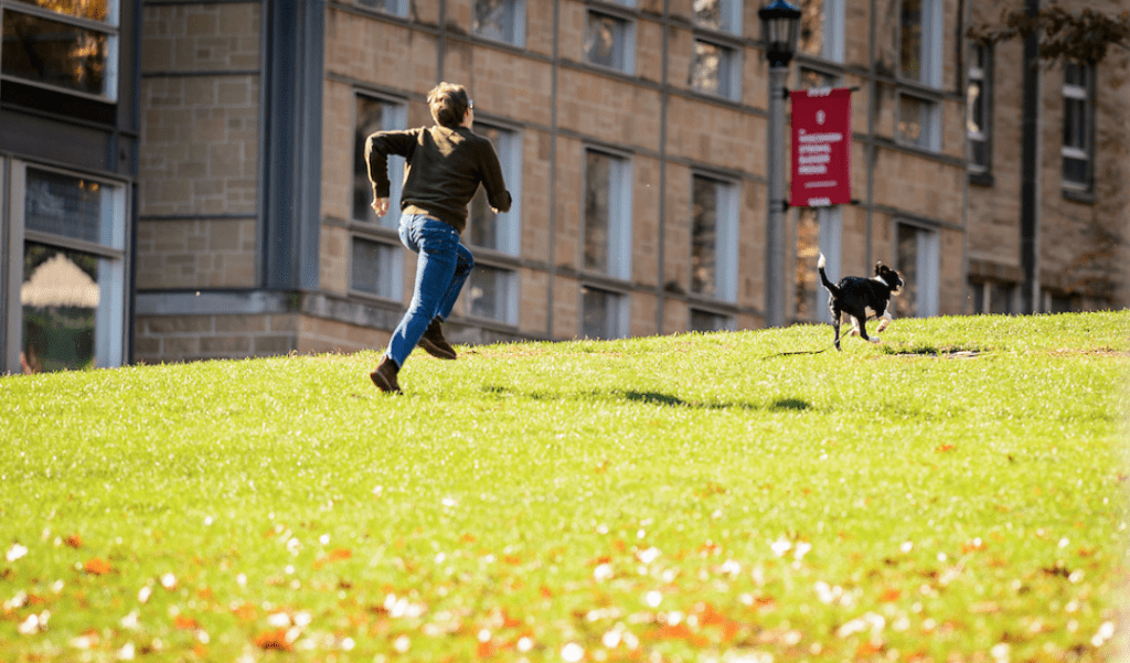 A photo of a student jogging up Bascom Hill with his dog.