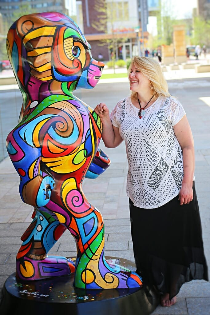 """Photo of Artist Julie Hustad standing next to """"Bucky come se Picasso,"""" an homage to Picasso's cubist paintings she designed for Bucky on Parade, a public art project."""