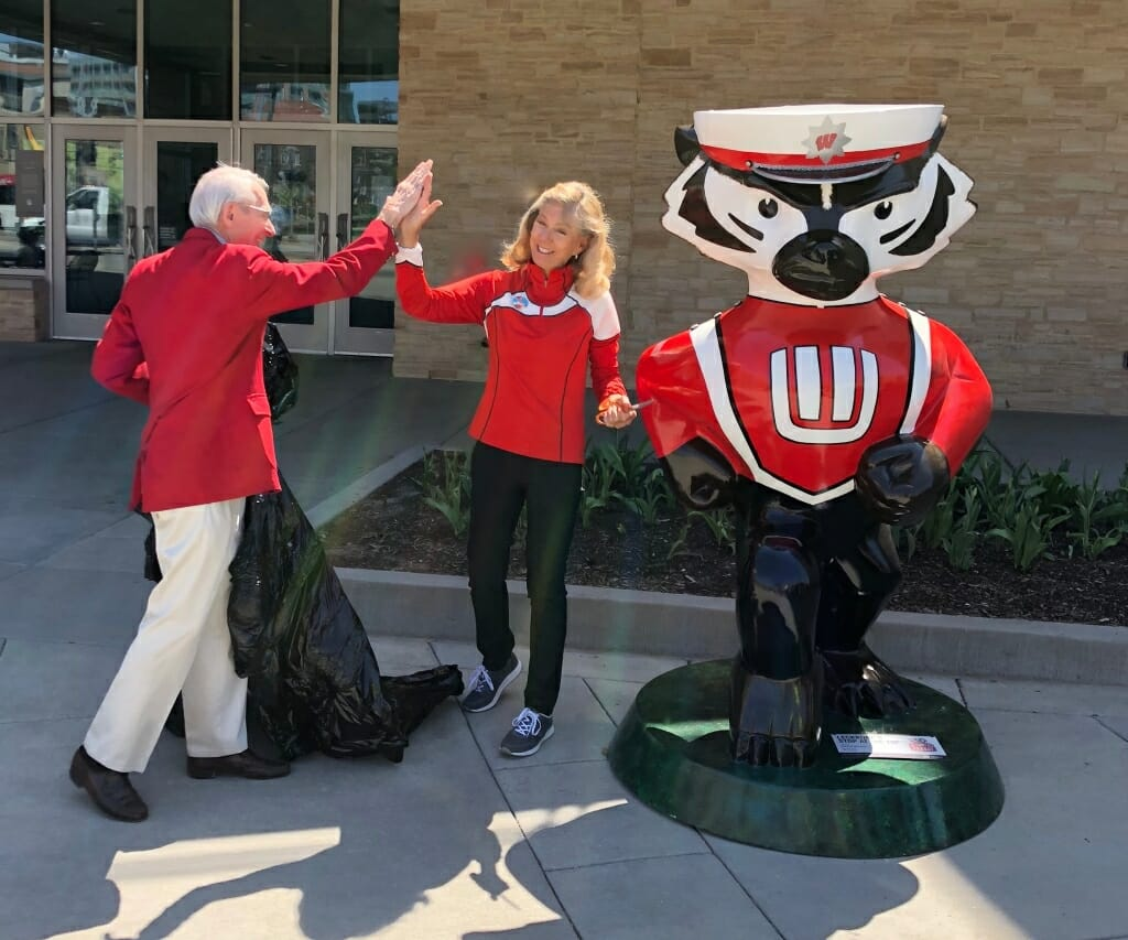 Mike Leckrone and Burgess celebrating next to the Bucky Badger statue after unveiling it.