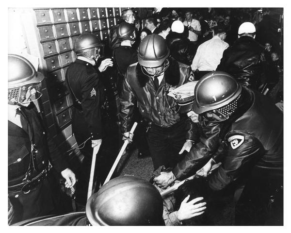 University of Wisconsin–Madison students clash with riot police during campus demonstration to protest Dow Chemical involvement in the Vietnam conflict. Here, several police officers with clubs hold a student down on the floor.