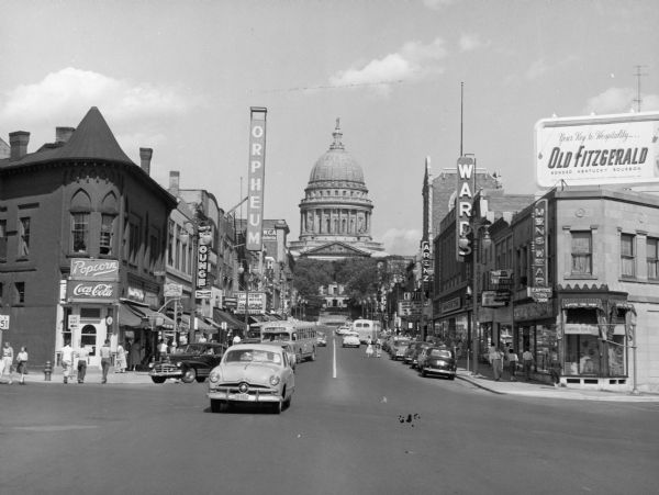 View up State Street towards the Wisconsin State Capitol taken from the West Johnson Street intersection. Businesses include the Orpheum Theater, Arenz, and Ward's. There is a billboard for Old Fitzgerald Kentucky bourbon on the roof on the right.