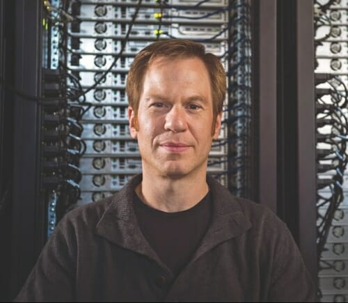 Photo: Dane Morgan standing in front of a computer taller than he is