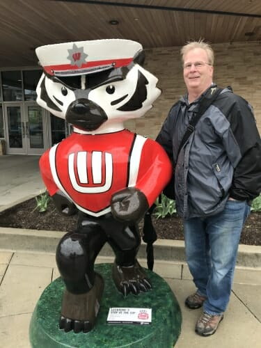 Photo: Helmkamp standing outside next to Bucky statue painted as UW Band member