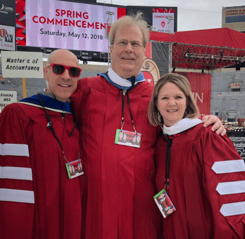 Photo: Argyle Wade in sunglasses, Kevin Helmkamp and Tonya Schmidt standing in red graduation gowns in front of Spring Commencement sign on jumbo-tron screen