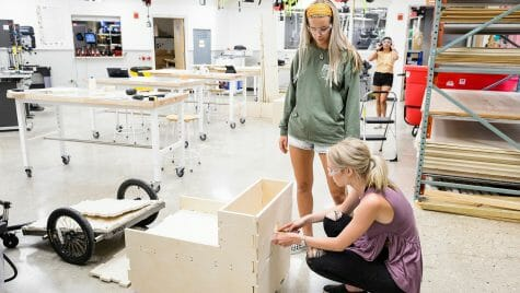 Undergraduates Montana Hodur, standing, and Rachel Johnson dry-fit fabricated parts for a portable garden prototype.