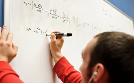 Photo: Person writing on whiteboard