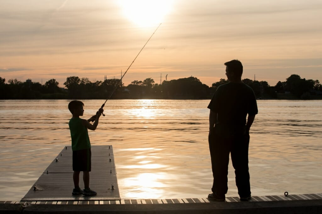 Photo: A boy casts a line into a lake as a man watches.