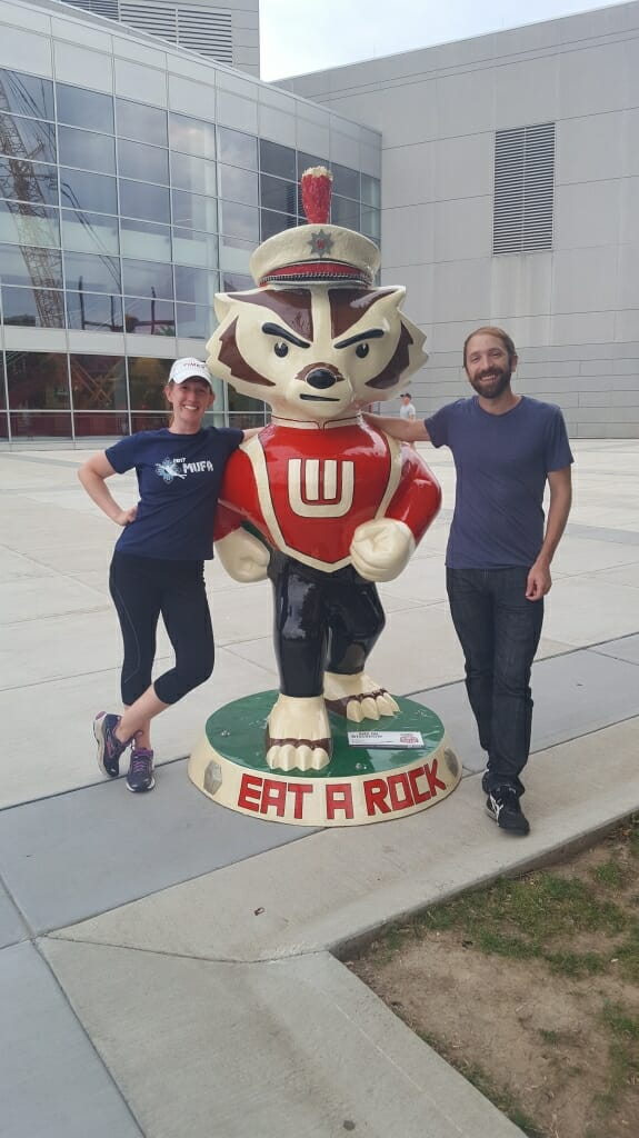 "Artist Jill Iwanski and her boyfriend Jake Ghilardi stand next to ""...And On Wisconsin!"" which Iwanski created for Bucky on Parade. The public art project saw local artists from across the state design 85 unique interpretations on Bucky Badger."