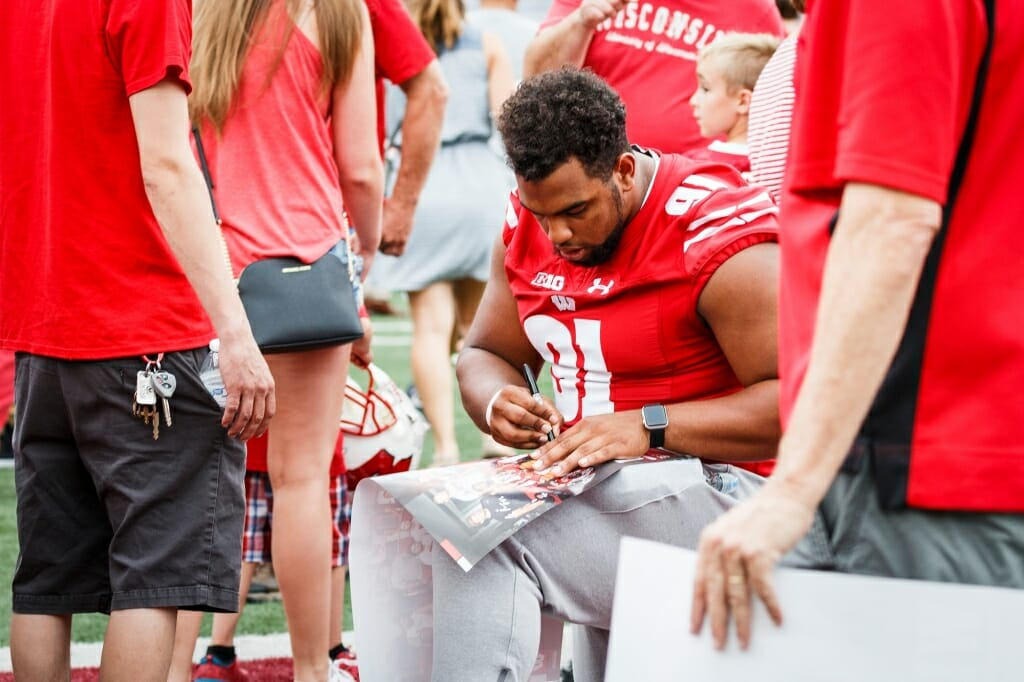 Wisconsin nose tackle Bryson Williams (91) autographs a fan's poster.