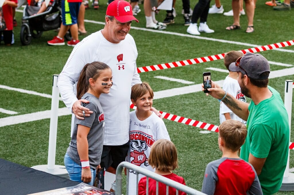 Head football coach Paul Chryst  poses for a picture with young fans.