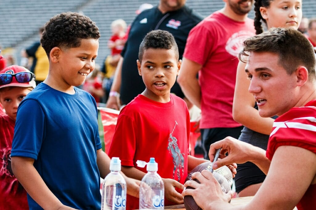 Young fans collect an autograph from tight end Kyle Penniston during Football Family Fun Day.