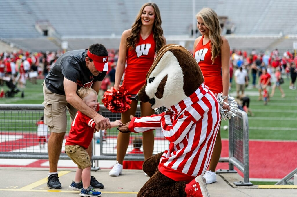 Bucky Badger and two cheerleaders welcome a young fan.
