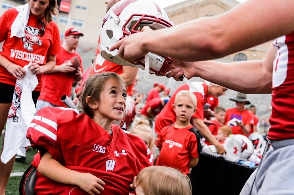 Isabella Stevens, 5, looks up in awe as she tries on shoulder pads and a helmet.