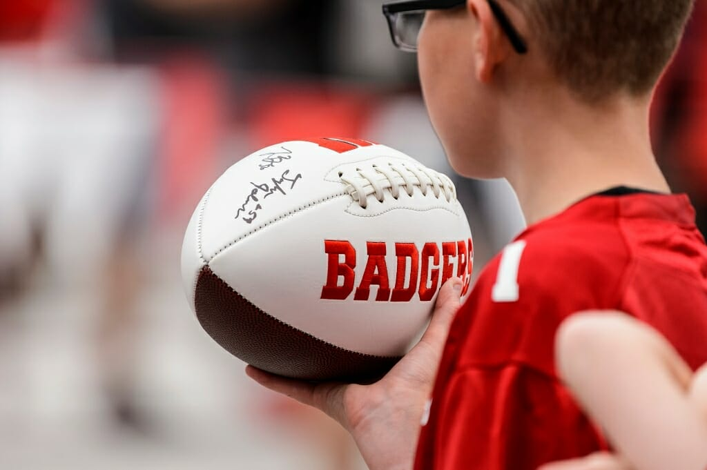 A young fan carries an autographed football.