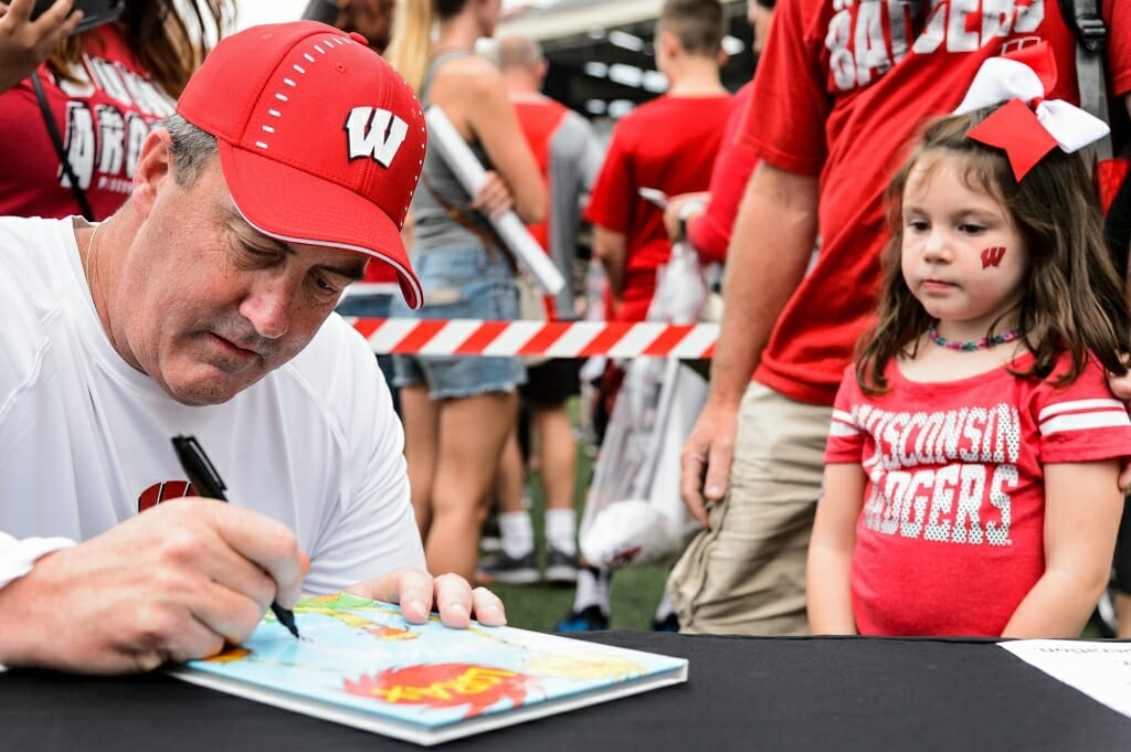 Football coach Paul Chryst signs Amia Riddle-Corey's book, The Lorax.
