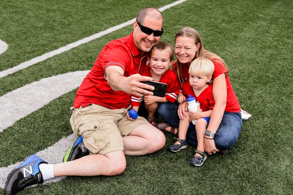 Clockwise from left, Dave, Val, Vin and Nat Schroeder pose for a family photo on the field at Camp Randall Stadium.