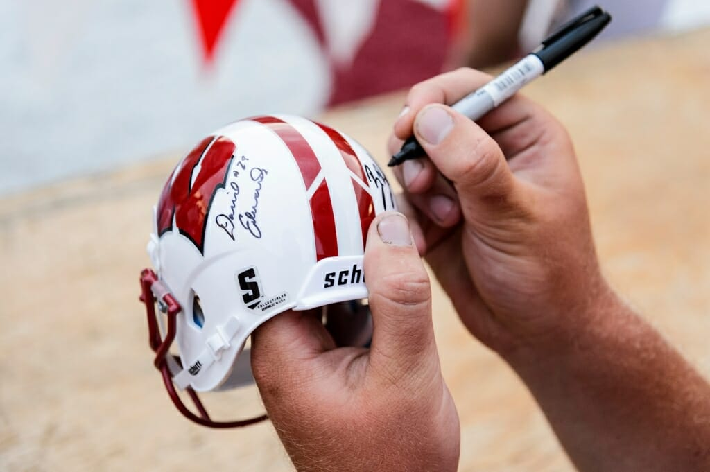 A player's large hands  dwarf a novelty helmet as he signs it.