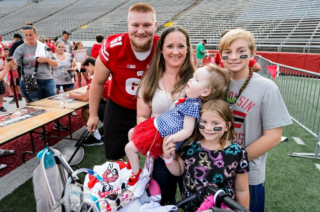 Wisconsin outside linebacker Tyler Biadasz (61) poses for a photo with mother Nicole Fritz and her children Leani (being held), J.R., and Daisy. Leani has spinal muscular atrophy and is a patient at the American Family Children's Hospital at UW-Madison.