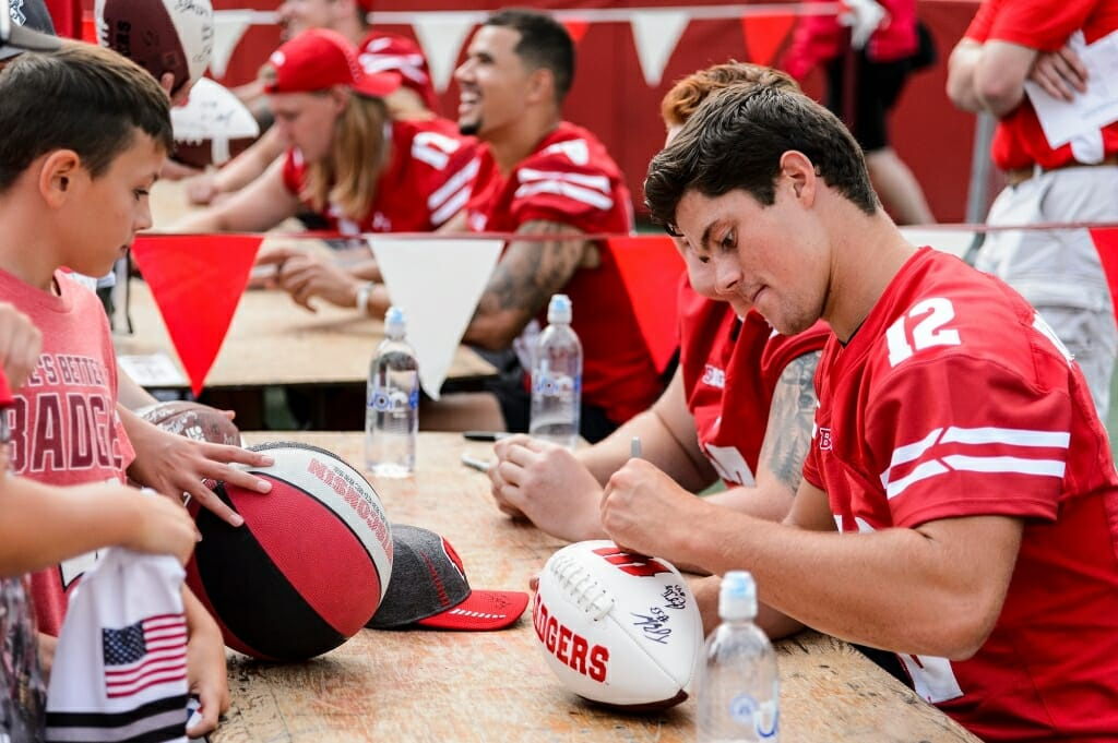 A young fan looks on as Wisconsin quarterback Alex Hornibrook (12) signs a football.